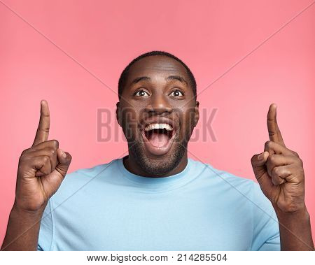 Excited Overjoyed Black Man Points At Copy Space, Sees Something Pleasant Upwards, Advertisizes. Hap