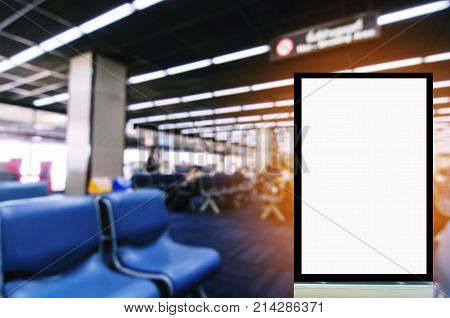 blank advertising billboard or showcase light box with copy space for your text message or media content with people in waiting room at airport background commercial and marketing concept