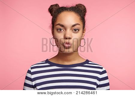 Cute Female Teenager With Black Skin, Two Hair Buns, Wears Earrings And Srtiped Sweater, Rounds Lips