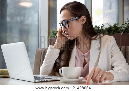 side view of a modern young business woman with long hair and glasses leading the conversation on the phone sitting at a table in a cafe with a laptop in formal attire