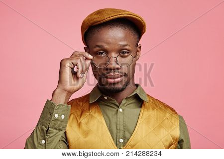 Confident Serious Dark Skinned Male Worker Has Clever And Intelligent Expression, Looks Through Spec