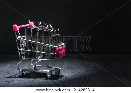 Metal Shopping Cart Or Trolley With Black Paper Bags On Wooden Background, Concept Of Black Friday