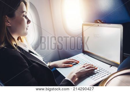 Young female student learning online via netbook while sitting in an airplane cabin.