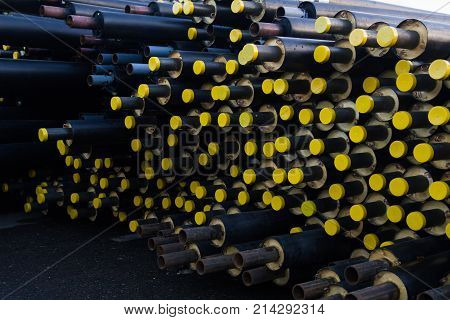 stored many black steel pipe with heat insulation on construction site in a plastic tube wrapper lying with yellow lids pipes for supplying gas heat pressure medium. photos from edge