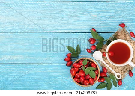 tea with rose hips on blue wooden background with copy space for your text. Top view.