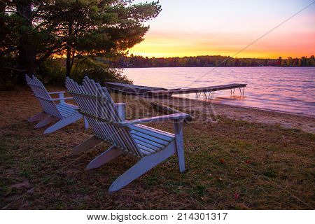 Summer Vacation At The Lake. Sunset over a lake with a row of Adirondack Chairs, dock and aluminum rowboat.