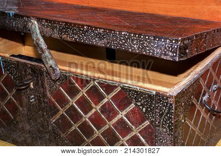 Semi-open big old wooden coffer, upholstered in wrought iron with geometric pattern squares. Close-up corner of coffer. Top side view.