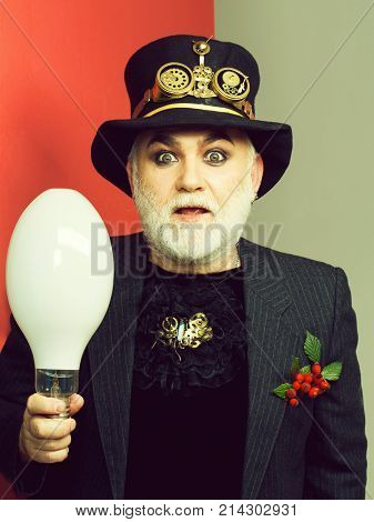 Amazed senior bearded man or watchmaker with white beard in black hat with watch mechanical metallic gears and cogwheels holds light bulb on grey red wall