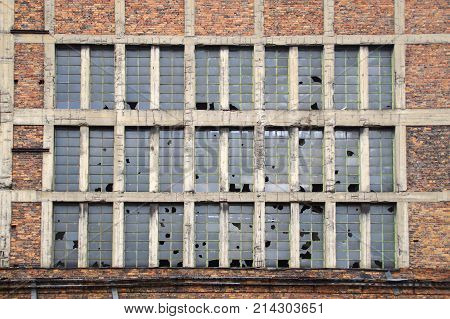 Big wall with broken glass. Forgotten brick building with destroyed windows.