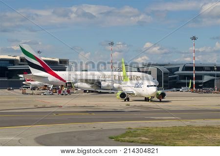 MILAN, ITALY - SEPTEMBER 17, 2017: Airbus A380-861 Emirates Airline and Boeing 737-800 airBaltic on the Malpensa airport