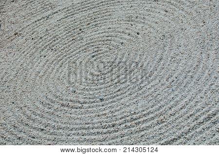 Zen circle shape white sand rock garden floor
