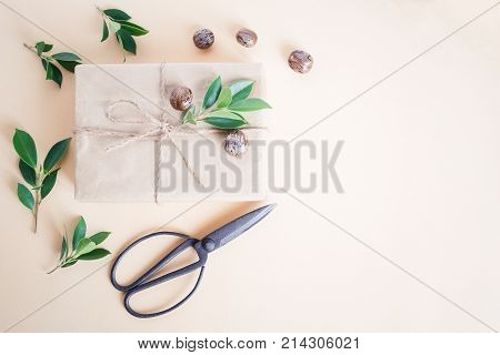 Brown gift box on yellow background handmade gift box and scissors christmas concept top view