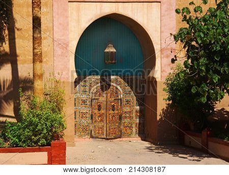 a historical colorful hidden in the alcove with typical semicircular shape wooden arabic gate. In the alcove a typical light is hanging