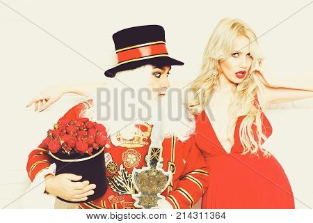 Curious senior man beefeater yeomen warder in uniform and pretty girl young sexy blond woman on white brick wall