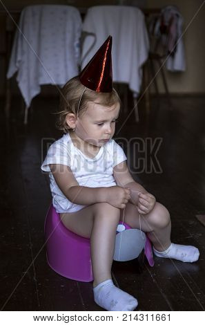 thoughtful sad child sitting on a potty with a paper party cap
