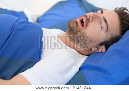 Man In Bed Suffering For Sleep Apnea Syndrome
