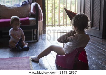 little baby sitting on a potty with party hat on the cottage with his younger sister