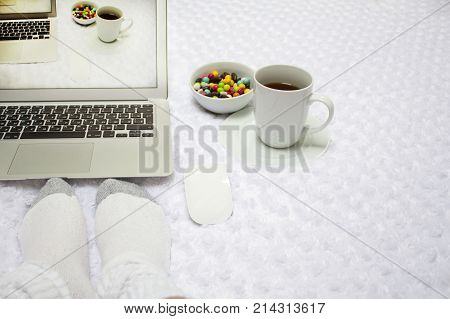 Laptop, a cup of tea, lollipops and female feet in white socks on a white blanket .  the image on the screen comes to life .  reality and picture on the screen are the same. Concept of escape to real.