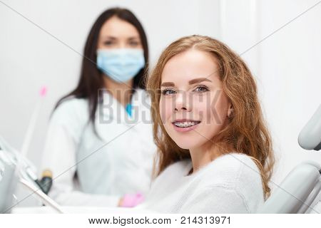 Happy red haired young woman smiling to the camera wearing braces her dentist posing on the background copyspace medical treatment appointment medicine healthcare dentistry teeth.