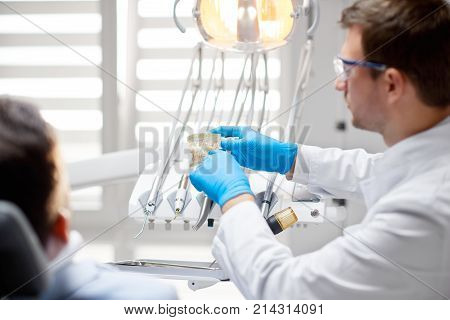 Selective focua on a dental mold professional mature dentist is holding while talking to his patient at the clinic profession occupation medicine health people model jaw oral dentistry concept.