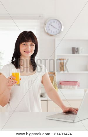Cute brunette woman holding a glass of orange juice while relaxing with her laptop in the kitchen