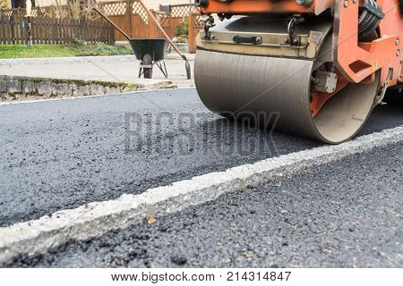 Sidewalk asphalt and compact with a road roller - close-up