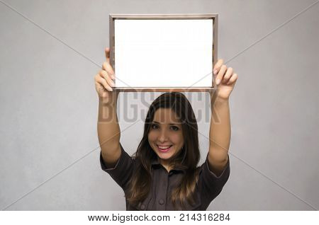Special offer. Young business woman in strict dress holding in hands empty blank photo frame above her head. Grateful letter. Gratitude concept. Thanks letter.