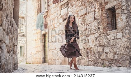 Cute Young Girl Walking In The Old Town. Nice Female Child In Medieval City.