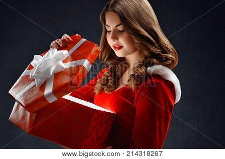 Young Snow Maiden in the red suit opens a big red gift for New Year 2018, 2019 and Christmas. She has pretty, smiling face and brown curly hair. She feels happy. The girl waits for winter holidays.