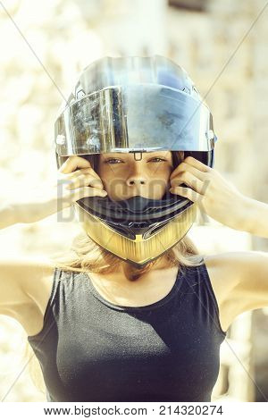 Pretty girl or sexy woman biker in motorcycle helmet and black undershirt on sunny summer day outdoors on blurred background