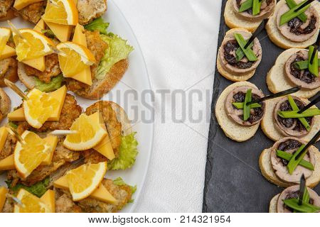 Two plates with snacks on a buffet table. Selection of tasty bruschetta or canapes on toasted baguette and quark cheese topped with fried meat or fish orange and green salad. restaurant feed. New Year Christmas. Top view