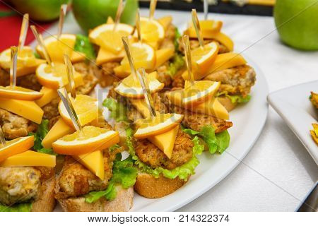 One plate with snacks on a buffet table. Selection of tasty bruschetta or canapes on toasted baguette and quark cheese topped with fried meat or fish orange and green salad. restaurant feed. New Year Christmas