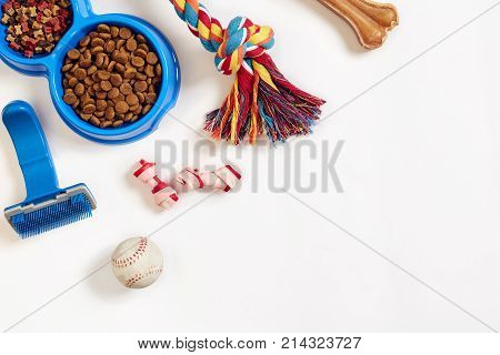 Dog care items, isolated on white background. Dry pet food in bowl, toy and bones. Top view. Copy space. Still life. Flat lay.