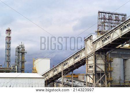 fragment of a modern industrial enterprise with silos for storage of loose materials fractionating columns and an inclined covered belt conveyor