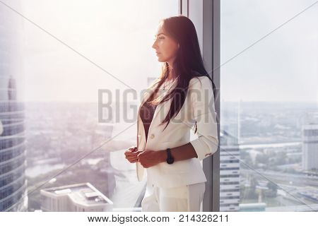 Portrait of pensive successful young woman boss standing near the window in office looking at cityscape thoughtfully