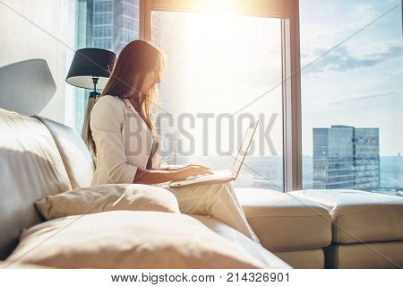 Side view of successful young female entrepreneur wearing formal business attire working on netbook at her luxurious apartment.