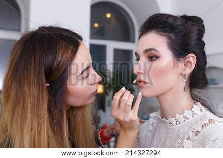 professional makeup artist doing makeup for young woman. Closeup portrait of make up artist at work in her studio. Makeup lips. Backstage photo as visagiste applying lip gloss