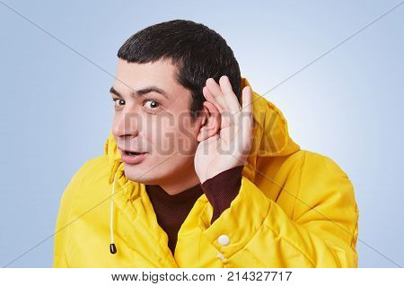 Curious Brunet Male Model Tries To Overhear Something, Keeps Hand On Ear, Listens Gossips In Next Ro