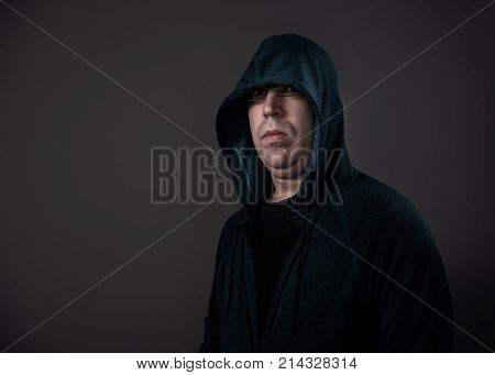 A man in his 30's wearing a hoodie shot against a grey background.