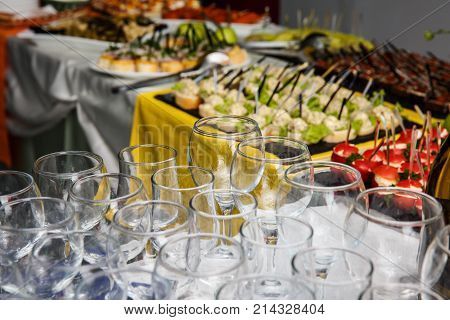empty glasses stand on a festive table with food preparation for the wedding feast on a buffet table