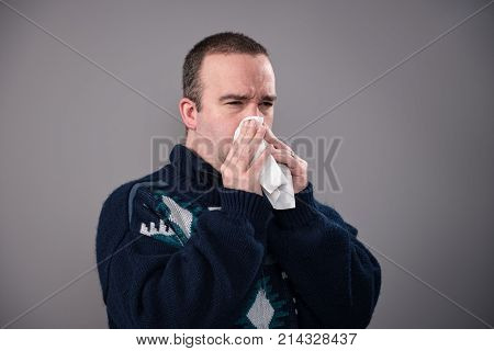 A sick man in his 30's is blowing his nose shot against a grey background