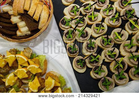 Two plates with snacks and bread on a buffet table. Selection of tasty bruschetta or canapes on toasted baguette and quark cheese topped with fried meat or fish orange and green salad. restaurant feed. New Year Christmas