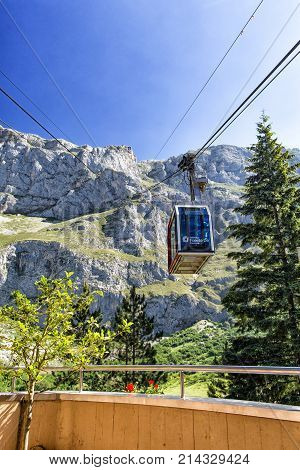 FUENTE DESPAIN - JULY 10 2016: The cabin of the ropeway Teleferico Fuente De goes to mountain top. A look from the place of landing a cabin against the background of huge gray mountains