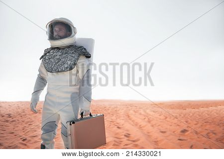 Concentrated spaceman wearing helmet is locating at desert and looking ahead with determination. Portrait. Low angle. Copy space on right side