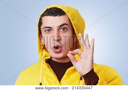 Cool Pleasant Looking Male With Dark Hair, Wears Yellow Anorak And Hood, Shows Okay Sign, Agrees Wit