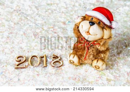 Wooden Figures Of 2018 On Snow. Christmas Atmosphere. The New Year 2018. A Toy Dog Is A Symbol Of Th