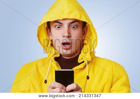 Shocked Pleasant Looking Male Looks At Smart Phone, Checks His Banking Account Online, Realizes That
