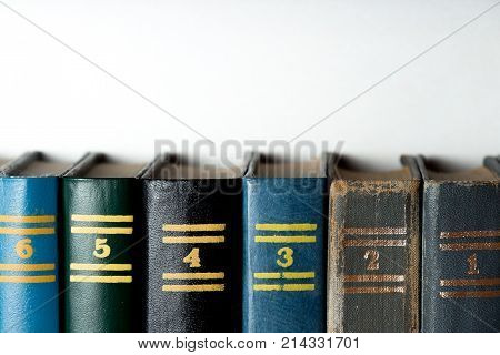 Books with numbers stand on a shelf against a white background