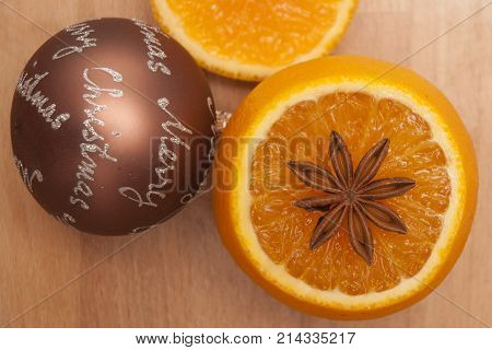 It is image of Christmas decoration with orange,Christmas ball and anise star