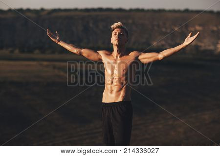 Handsome bare-chested man standing in nature and holding his arms wide open.